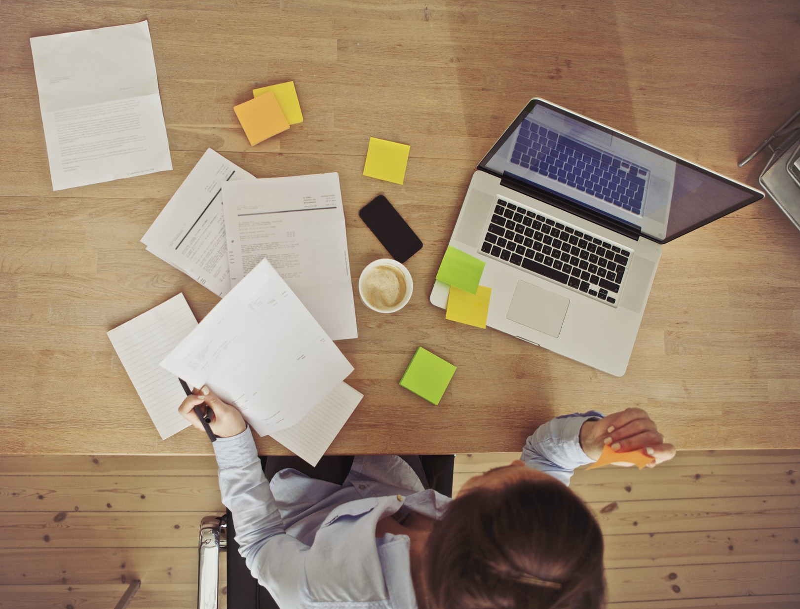 Top view of young woman working at her desk with laptop and documents. Business woman working at desk in office.
